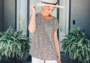 Model standing in front of front door wearing a leopard print short sleeve top with white shorts and a straw sun hat.