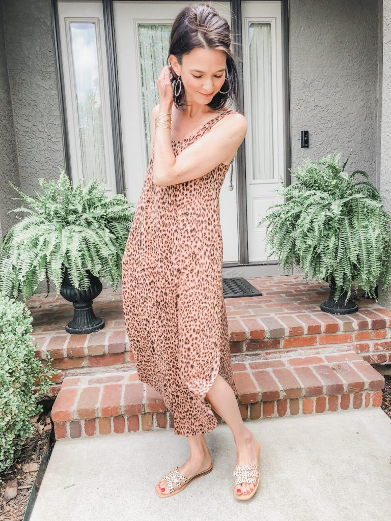 Model standing in front of front door wearing a leopard print maxi dress.