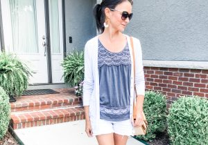Model wearing dark gray tank top with cardigan and white denim shorts