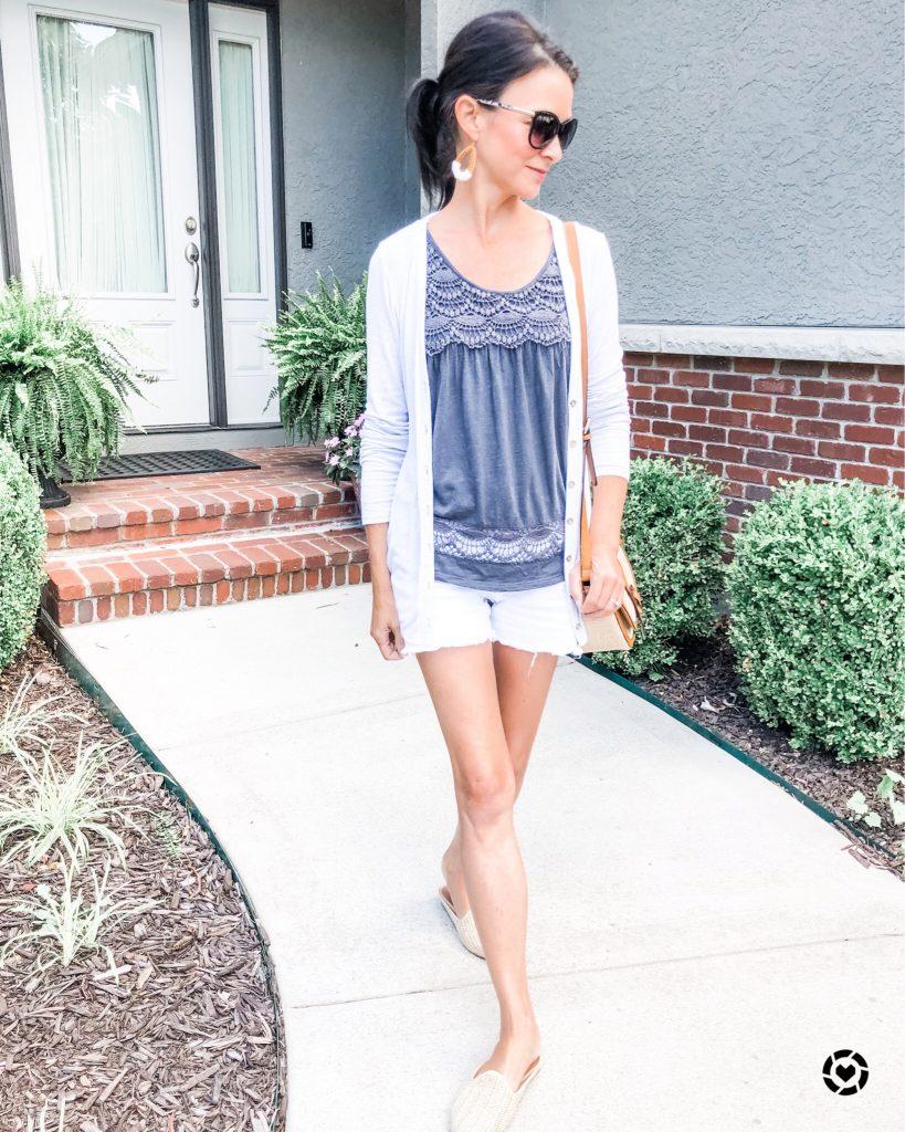 Model walking down sidewalk wearing white denim shorts, a tank, top, cardigan, and sunglasses.