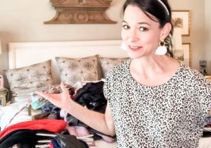 Dark haired lady standing in front of clothes piled on top of bed for a closet clean out.