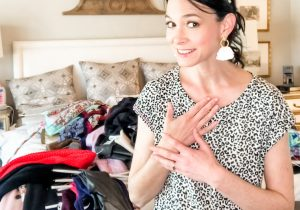 Brunette lady standing in front of bed with clothes piled on top of the bed from the closet.